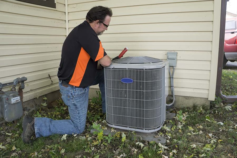 AC repair technician working on air conditioning unit.