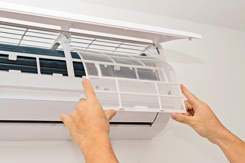 A pair of hands adjusting a ductless system | What Maintenance Is Needed for a Ductless System? | Boone
