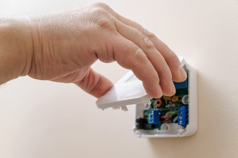tips to troubleshoot your thermostat, hand lifting thermostat cover