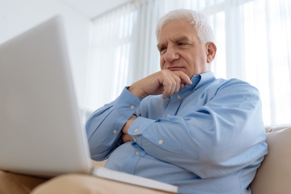 What's that sound coming from my furnace?, Elderly man sitting on comfy sofa and watching something on laptop,