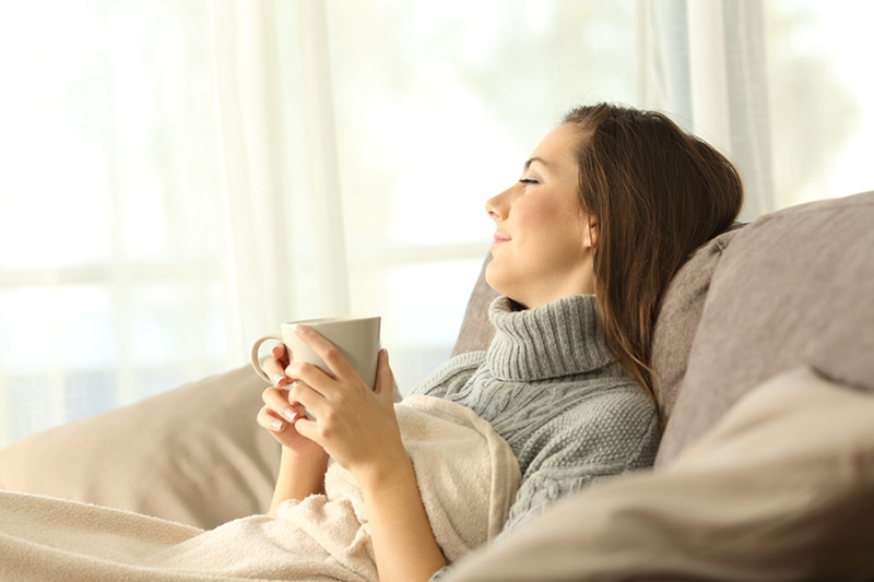 What Are Zone Control Systems? Portrait of a pensive woman relaxing sitting on a sofa in the living room in a house interior in winter