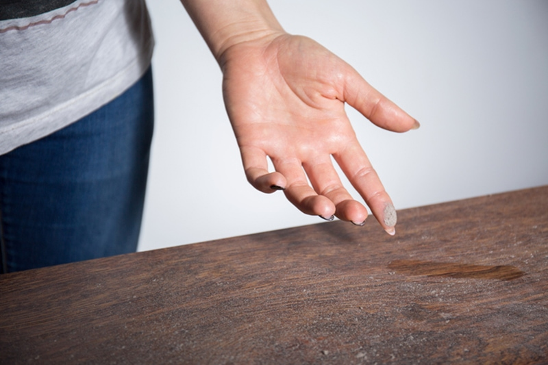 How to Eliminate Dust in My Home, Close-up of dust on woman finger taken from wooden table