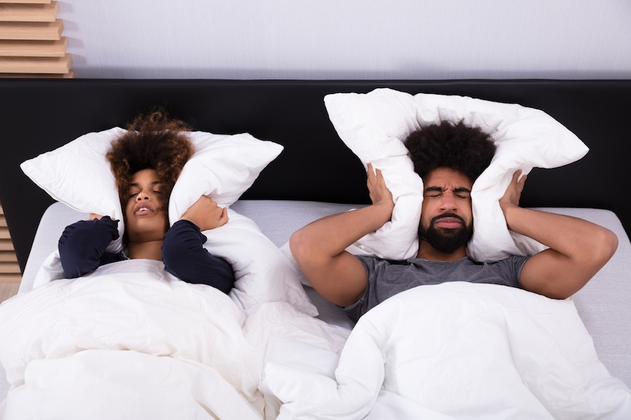 Elevated View Of Young Couple Lying In Bed Covering Their Ears With Pillow.