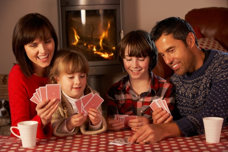 Portrait Of Family Playing Cards By Cosy Log Fire Sitting At Table Having Fun