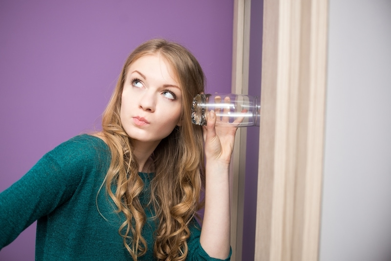 Curious young woman with glass leaning against the door listening to a conversation