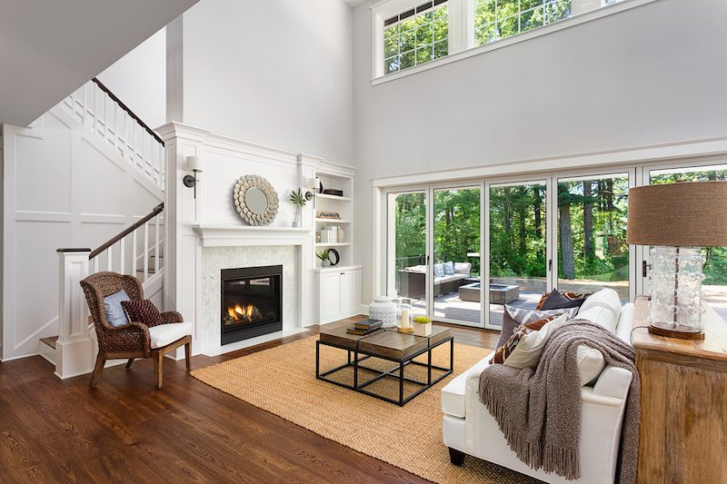 Beautiful living room interior with hardwood floors and fireplace in new luxury home with sliding glass doors and vaulted ceiling. Know the different types of furnaces for your home.