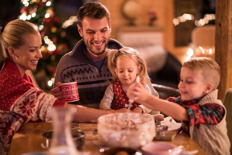 Happy family having fun while preparing a cake on Christmas Eve at home. Focus is on father and daughter.