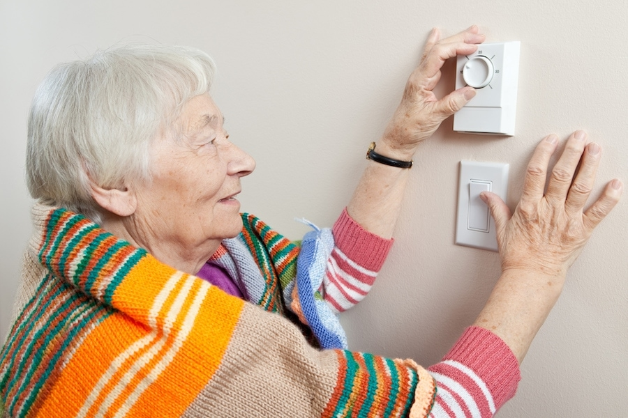 Old lady adjusting thermostat.