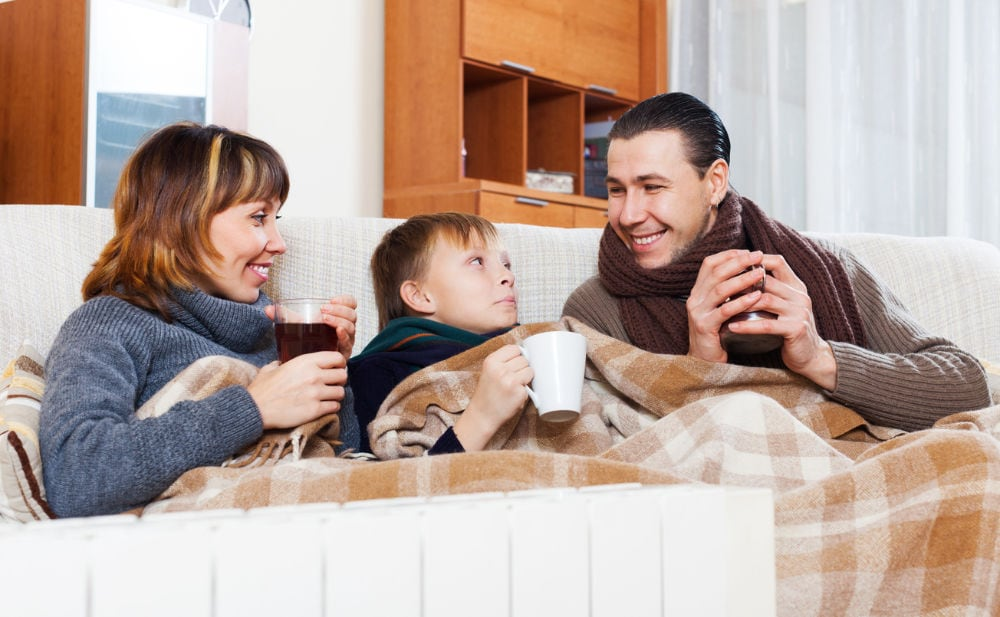 Family of three keeping warm in cold home.