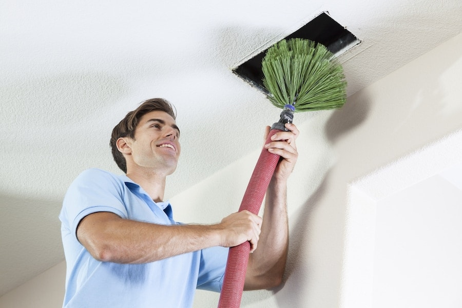 Technician cleaning air ducts in home